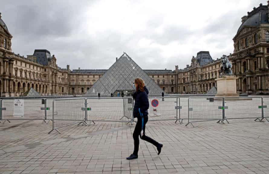 A pedestrian crosses the courtyard in front of the Louvre Museum in Paris as France prepares for a new lockdown.