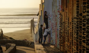 A man climbs up a section of a US-Mexico border wall in Tijuana, Mexico, on Christmas Eve.