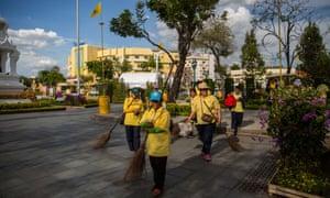 Volunteers sweep near the Thai royal palace ahead of the coronation.