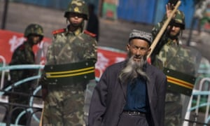 An ethnic Uighur man passes by security forces in Urumqi. The US has denounced China's treatment of the Muslim minority.