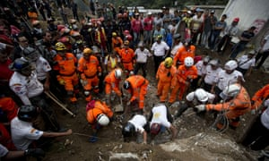 Rescue workers and firemen search for survivors in Cambray near Guatemala City on Friday.