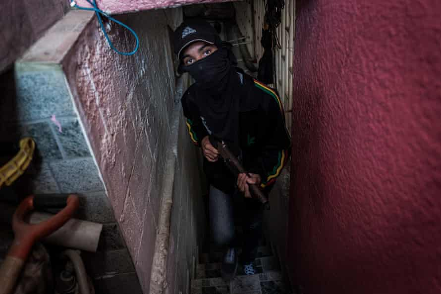 Freddy, 16, a member of a kidnapping gang, guards a safe house in a slum in Caracas. He too, joined a gang to find food for his family