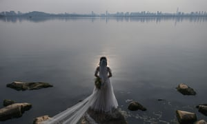 A bride poses for photographs next to East Lake in Wuhan, 19 April