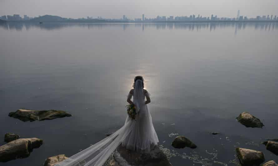 A bride, poses for a wedding photographer next to East Lake in Wuhan