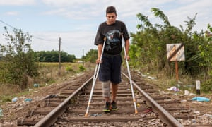 Hassan Hassanein, 14, makes his way on crutches as he crosses into Hungary from Serbia on an abandoned railway line.