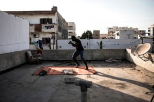 Senegalese wrestler Moussa Diop shadow-boxes on his rooftop in Dakar.