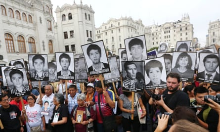 People holding pictures of victims of the guerrilla conflict march against President Kuczynski's pardon for former president Alberto Fujimori in Lima