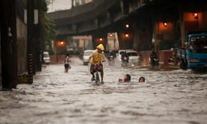 A Filipino on a bike passes children in a flooded street in Manila, the Philippines, in 2016.