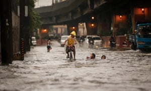 A Filipino on a bike passes by children frolicking along a flooded street. Heavy monsoon rains have resulted in floods across Manila