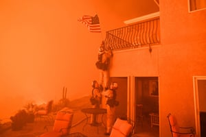 Firefighters remove a US flag on a luxury home in Oroville