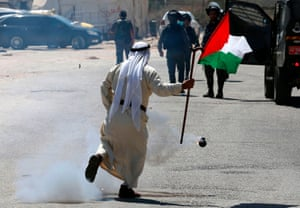 West Bank, PalestineA Palestinian demonstrator runs past a teargas canister fired by Israeli forces during a protest