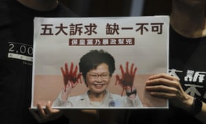 Pro-democracy lawmakers hold placards with a picture of Hong Kong leader Carrie Lam with blood on her hands.
