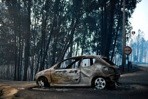 A burnt car on a road after a wildfire in Pedrogao