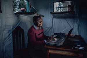 Patrick Byamungu sits in his office where he provides free WiFi to the community