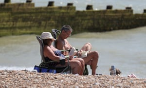 Holidaymakers reading on Eastbourne beach, East Sussex.