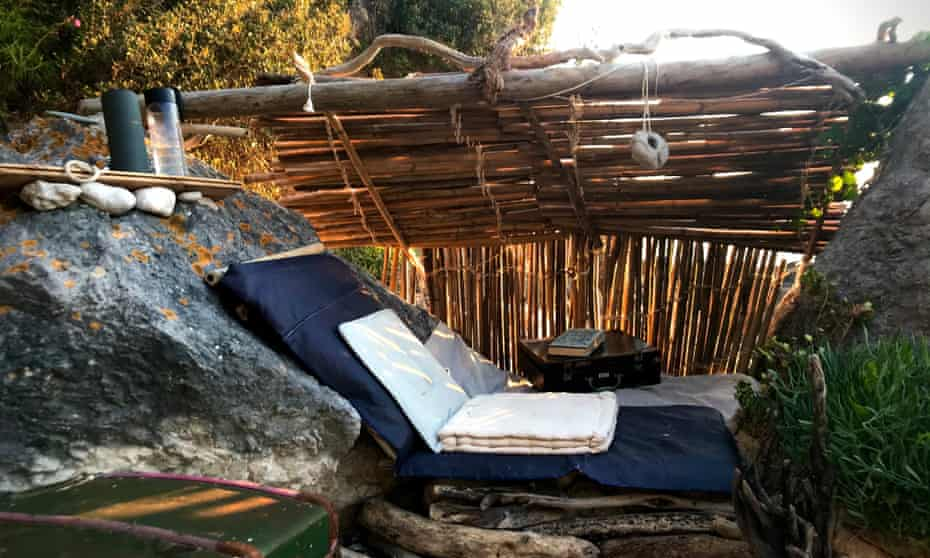 Susan's den, showing the bamboo roof and a blue mat for sitting on against the rock