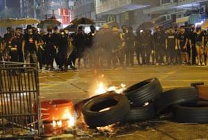 Black-clad protestors stand near burning tires in Hong Kong.