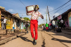 """In this image, Stephen Okoth walks down a street in bright red trousers and floral shirt, while carrying a cathode ray TV on his shoulder. It is a bright sunny day in Nairobi. In the Kibera neighbourhood of Nairobi, Stephen Okoth, also known as Ondivour, is a film-maker, photographer and model for his self-styled colourful and vintage fashion. """"He inspires a generation in the shanty town through his sense of style, which brings so much hope and vibrancy to the people,"""" says photographer Brian Orieno, who submitted this image to the #CelebrateAfrica competition hosted by fairtrade photo agency Picfair and New African magazine, and sponsored by Canon. The competition was open to residents of all African countries and the winners will be announced on 3 May."""