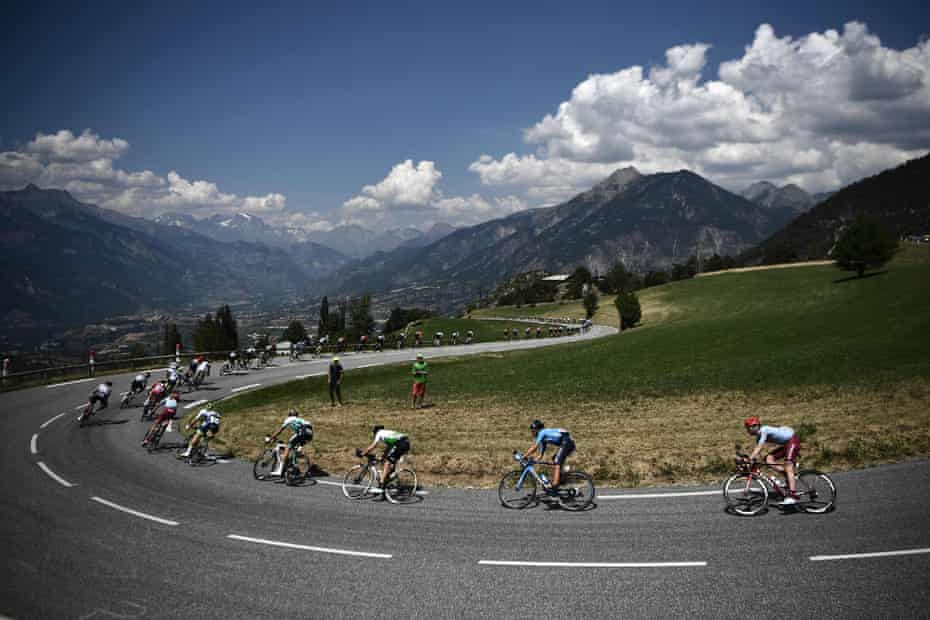 Cyclists take a curve with mountains in background during stage 18 between Embrun and Valloire.