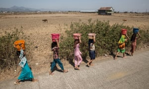 Girls carry buckets of clean water through drought-affected land near Makassar, Sulawesi, Indonesia