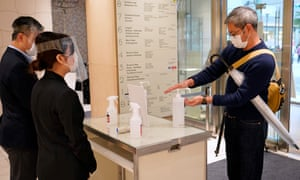 A customer uses hand sanitiser as he enters a Tokyo shopping centre.