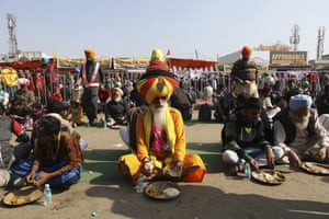 Farmers eat their lunch at the Delhi-Haryana border on the outskirts of New Delhi