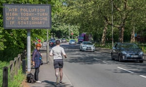 A jogger passes air pollution warnings on the busy South Circular road in London