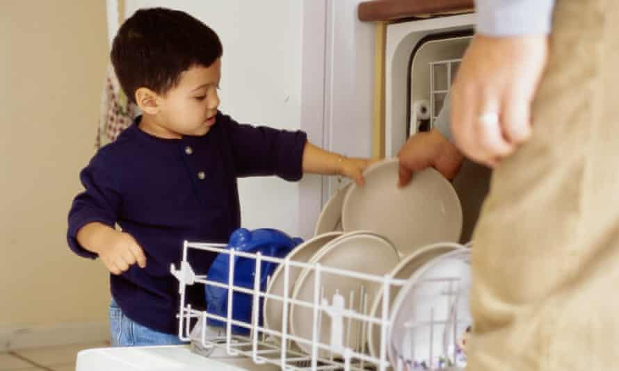 Toddler helping unload dishwasher