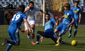 A Tavria player (in white) fights for the ball during a 2015 home cup match with SKChF Sevastopol at the Lokomotiv stadium in Simferopol.