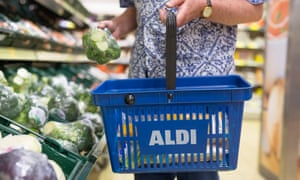 A shopper in Aldi buying Broccoli