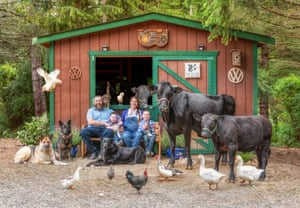 A family pose with their animals, which include cows, dogs and ducks