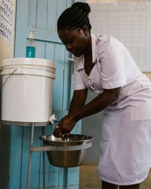Nurse-midwife Jackeline Gideon Mwiguta washes her hands using at Nyarugusu Dispensary