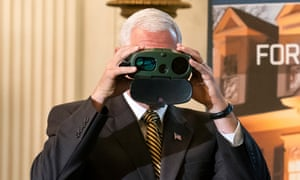 Pence looks through a pair of FLIR binoculars while touring the showcase