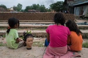 Children sit outside the kilns