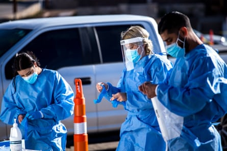 Medical workers put on personal protective equipment (PPE) before starting shifts at a Covid-19 drive-thru testing site in El Paso, Texas, U.S., on Monday, Nov. 9, 2020. Texas recorded more than 9,000 new cases in a 24-hour period last week, the steepest daily increase since Aug. 4, according to state health department figures.