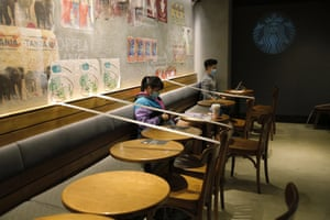 Tables and chairs of Starbucks are taped for social distancing law enforcement