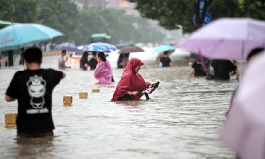 People walk along a flooded road in Zhengzhou