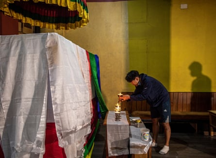 Phurba Tshiring Sherpa, a grandson of Ang Rita Sherpa, lights candles in front of his casket in Kathmandu.