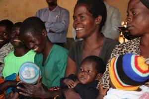 Mothers wait for their five-month old children to receive the first dose of the malaria vaccine