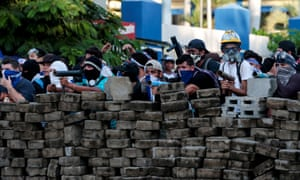 Demonstrators stand behind a barricade during a protest against President Daniel Ortega's government in Managua on 30 May.