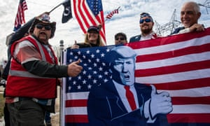 Trump supporters hoist a flag and give the thumbs-up.