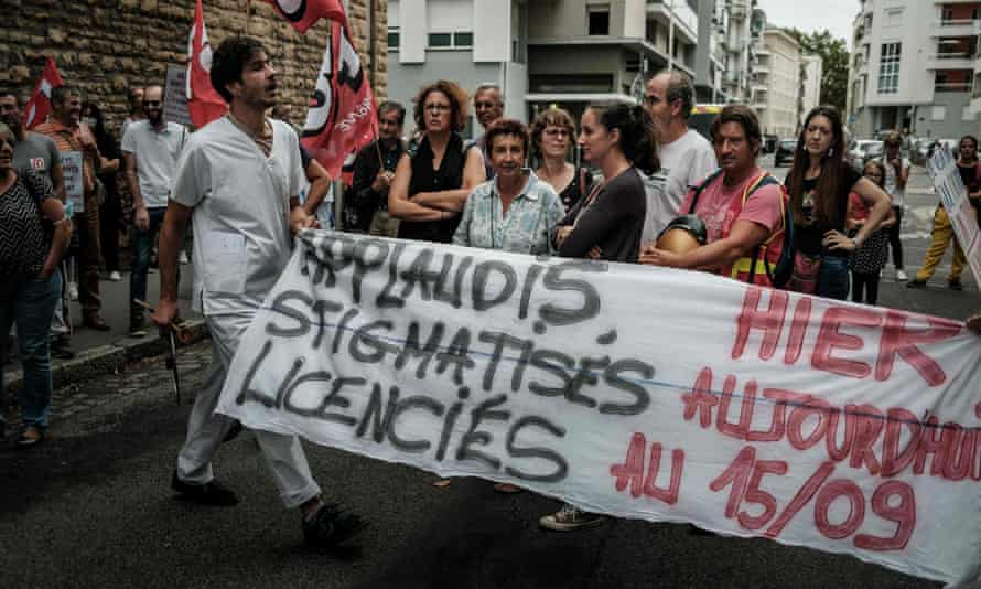 Demonstrating nursing staff in Lyon displaying a banner that says: 'Applauded yesterday, stigmatised today, made redundant on 15/9.'