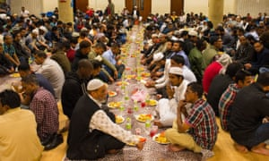 Muslims prepare to eat iftar, the evening meal to break fast during Ramadan, at the East London mosque, in Whitechapel, London.