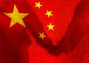 People holding hands behind a Chinese flag.