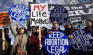 Pro-abortion rights counter protesters hold signs while anti-abortion demonstrators march past the Supreme Court in Washington 22 January 2015.