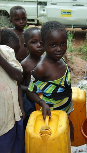 Girl carries two jerry cans for water
