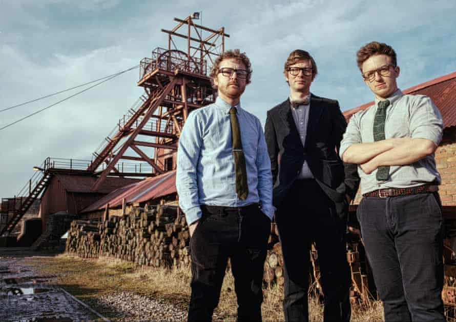 public service broadcasting standing by a woodpile at a pit head