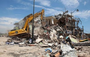 A crane operates on the rubble of a collapsed building in Pedernales
