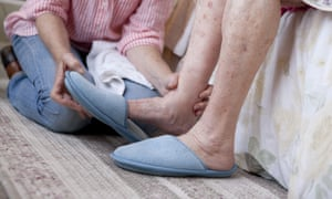 A woman helping an elderly woman put slippers on