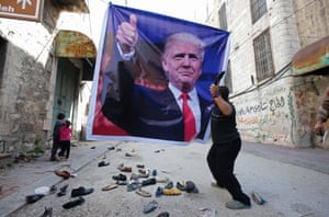 A Palestinian demonstrator throws a shoe at a poster of Donald Trump in Hebron, West Bank